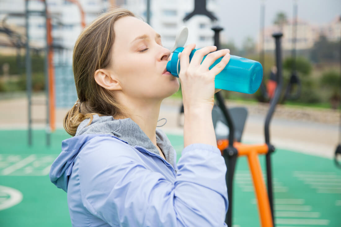 girl drinking electrolyte drink during workout image